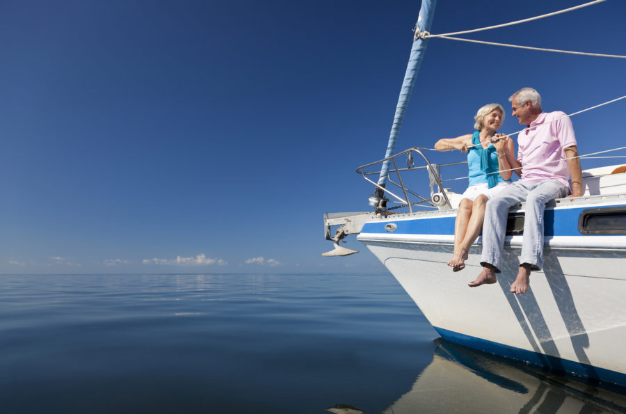 A happy senior couple sitting on the front of a sail boat on a calm blue sea