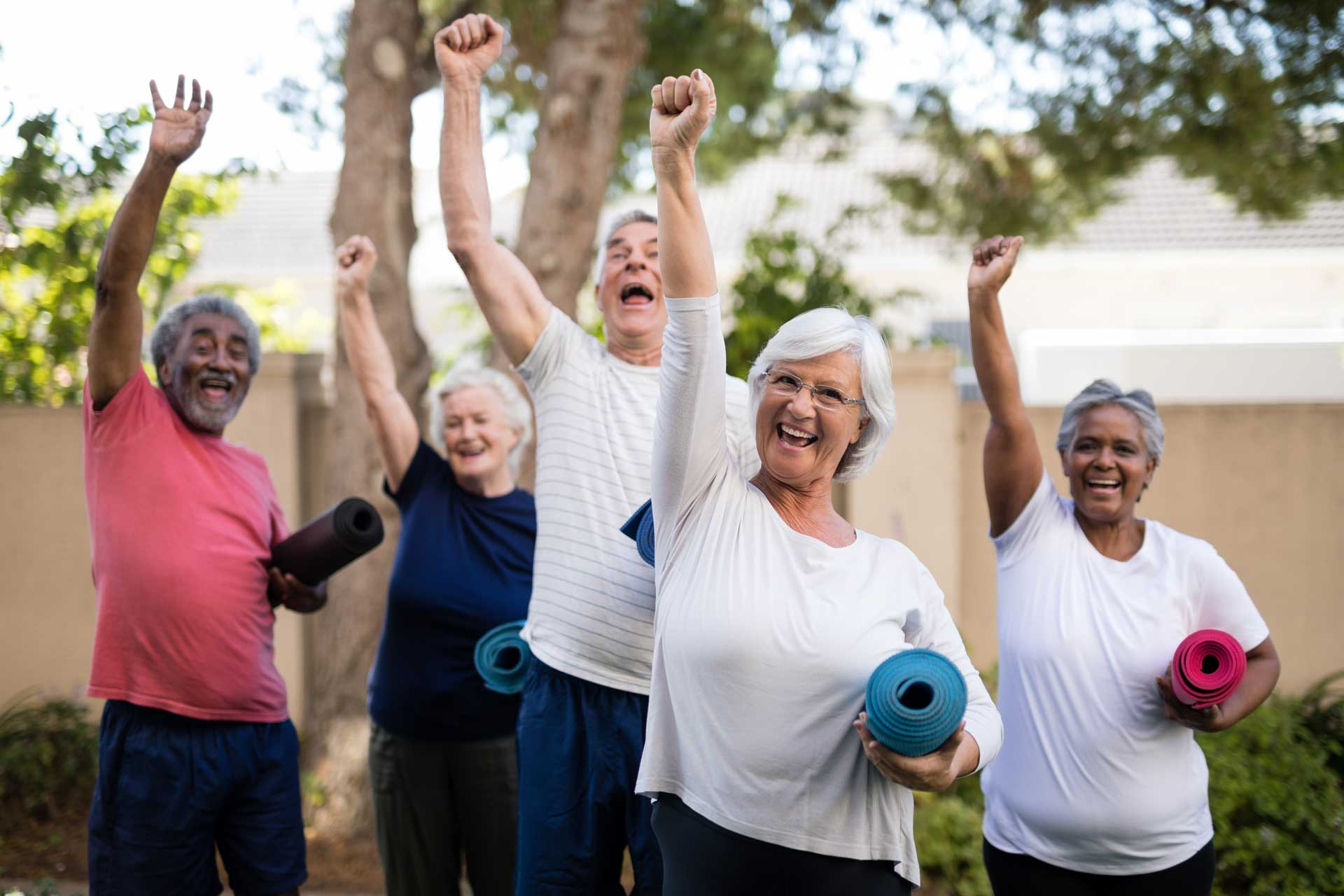 Cheerful seniors with exercise mats at park