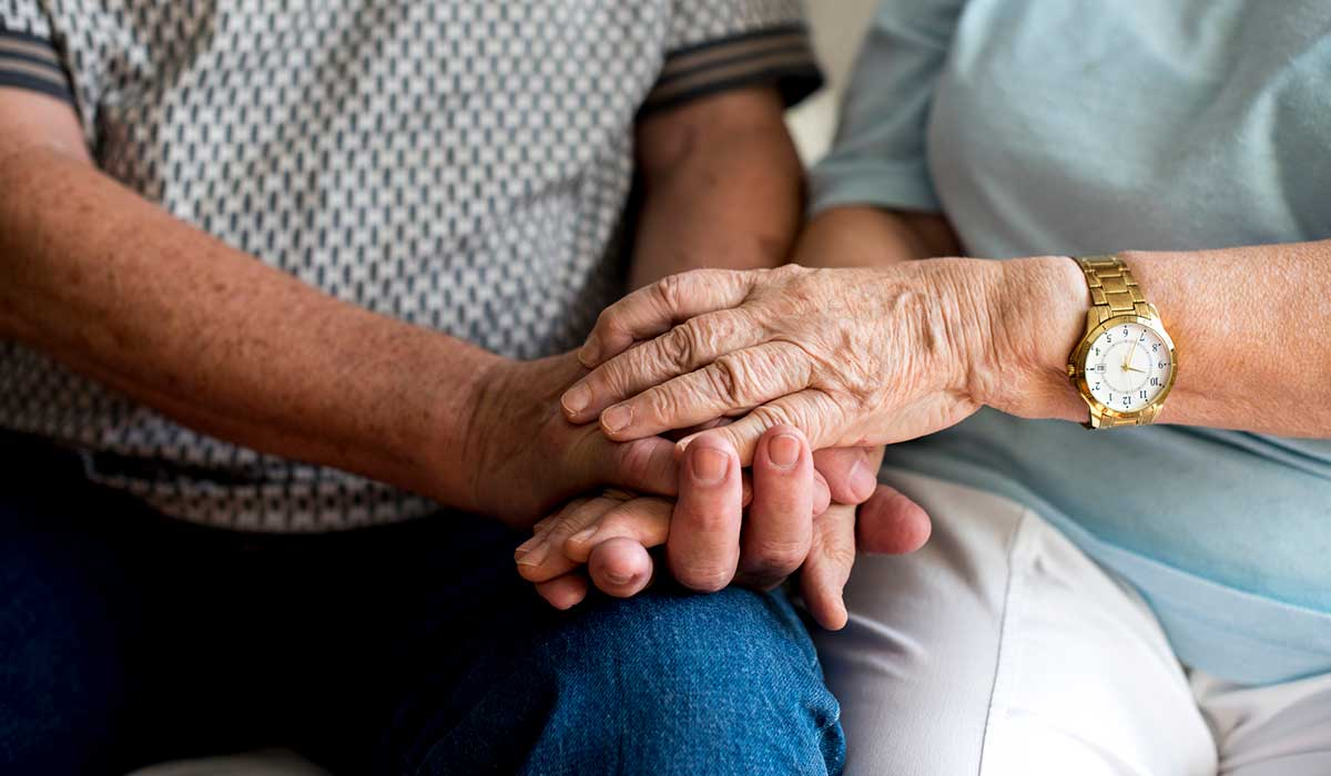 an elderly couple holding hands
