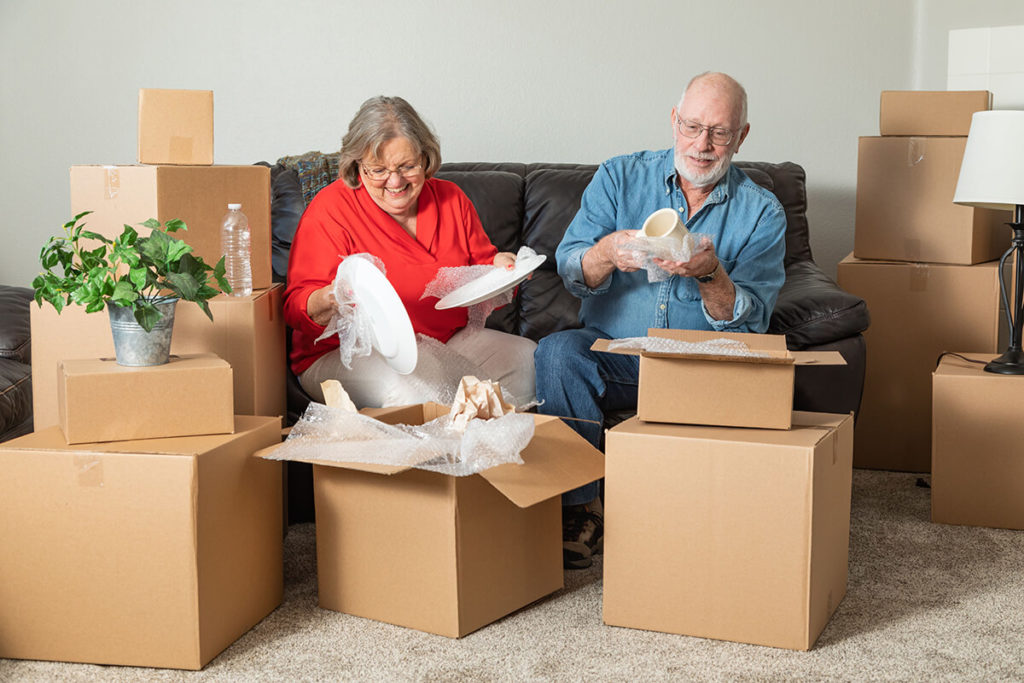 A happy couple sitting on their couch surrounded by boxes as they unpack belongings