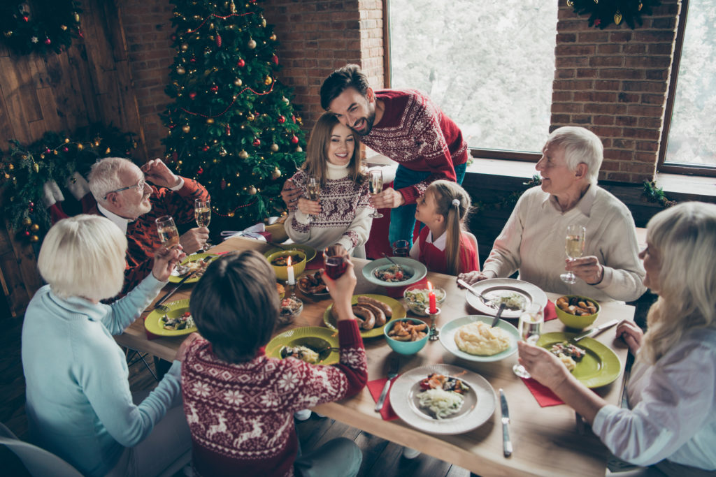 a family settling in to enjoy a family dinner during the holidays