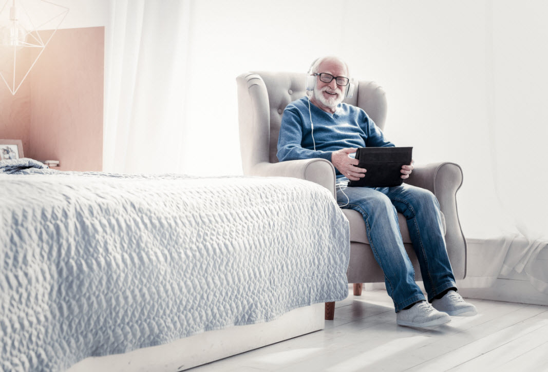 a senior resident listening to music on his tablet
