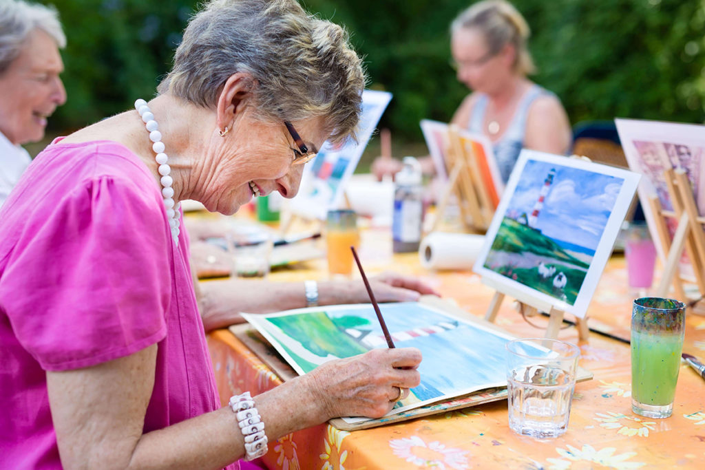 residents taking part in a safe outdoor group painting session