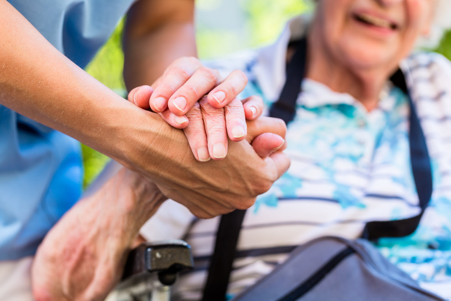 the hand of a registered nurse attendant holding the hand of a senior resident