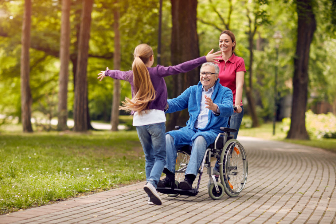 cheerful grandfather in a wheelchair opening arms to welcome a hug from visiting family member