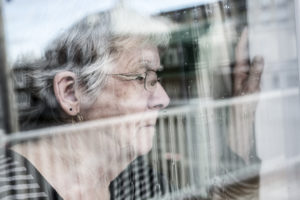 A Senior woman looking out through a window